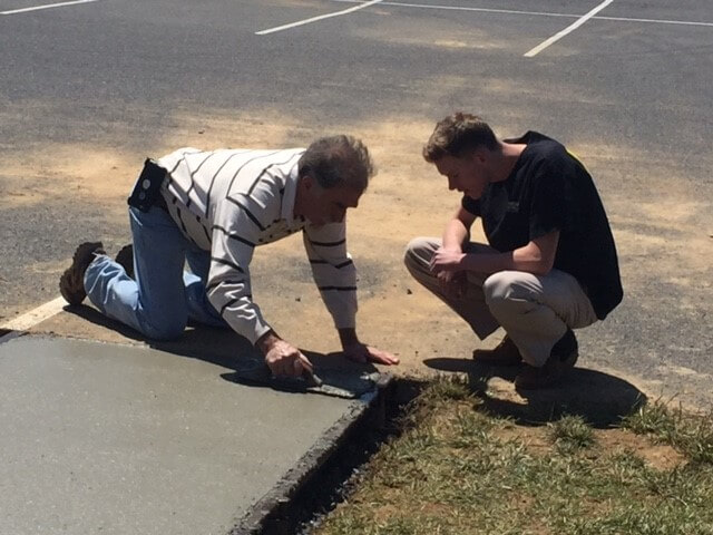 older man teaching young adult how to hand spread cement for a new sidewalk with trowel