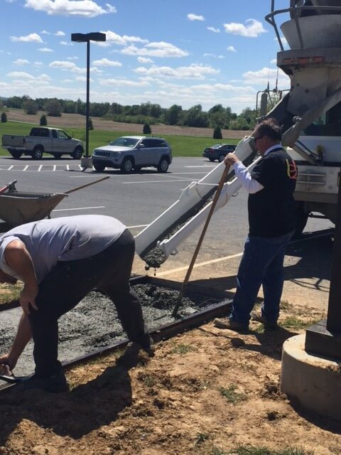 men pouring concrete for new sidewalk
