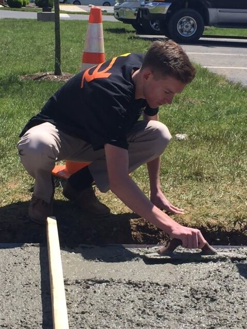 young adult man hand spreading cement for a new sidewalk with trowel